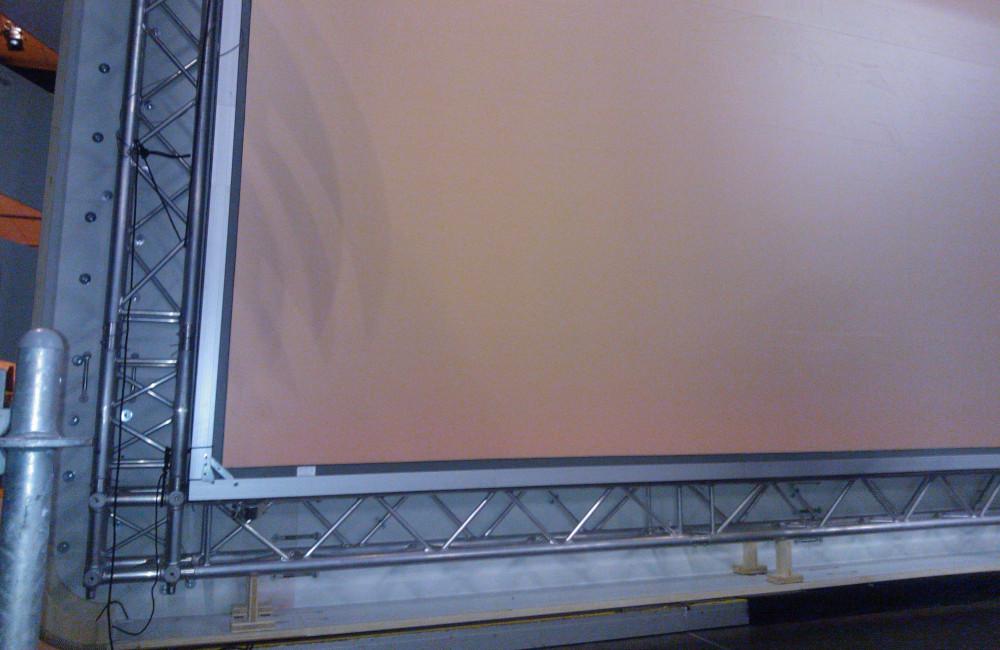 Bühnenkulisse mit tragendem Traversensystem und fertig montierter 8m breiten Rückprojektionsleinwand in der Messe Klagenfurt
