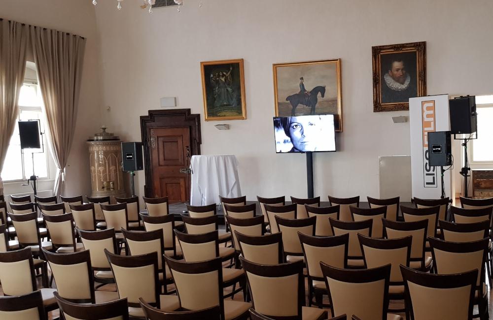 Vortragssaal mit Bühne, Flat-TV auf SMS Stativ und Meyer Sound Lautsprechern auf Stativen in Klagenfurt Schloss Maria Loretto