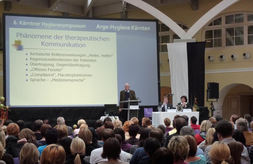 Bühne mit 6m breiter Rückprojektion, Rednerpult und Meyer Sound Lautsprecher auf Stativ im Krankenhaus Friesach