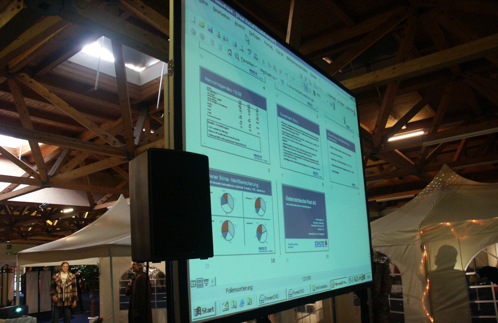 Videoprojektion auf Rückprojektionsleinwand und PA Lautsprecher auf Stativ in der Messehalle Klagenfurt