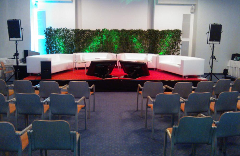 Bühne mit Sofas, Beistelltischen, Vorschaumonitoren, Meyer Sound Lautsprecher (Monitor und PA) im Warmbad Villach GKK