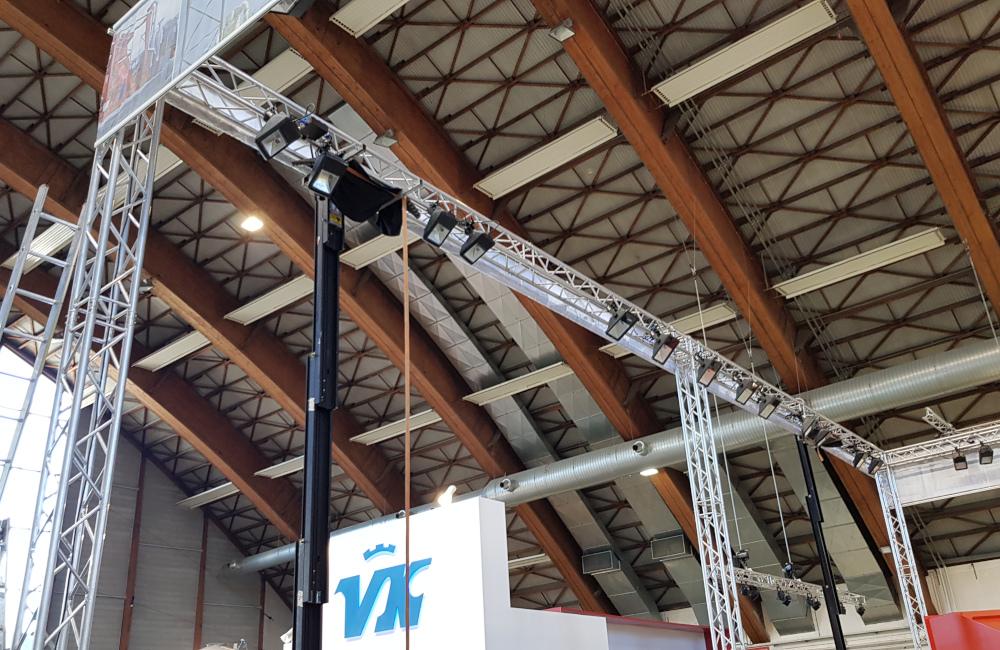 Rudnick & Enners Messestand Aufbau der Traversen, Banner und HQI Beleuchtung auf der Messe Holzbau in Klagenfurt