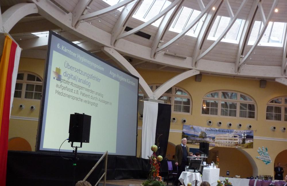 Konferenz Bühne mit Rückprojektion Meyer Sound PA und Rednerpult beim Hygienesymbosium im Krankenhaus Friesach