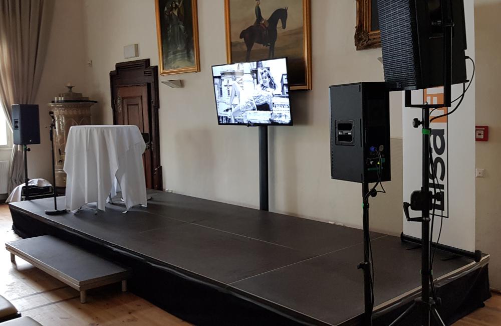 Bühne mit Stufe und Verkleidung, Meyer Sound Lautsprecher, Flat-TV für Lisafilm Buchpräsentation Schloss Loretto Klagenfurt